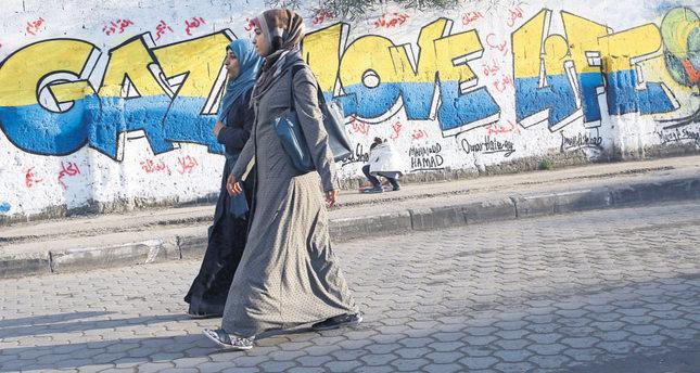 Two female Palestinian students walking past a graffiti reading GAZA LOVE LIFE in Gaza City, on Dec. 30, 2015.