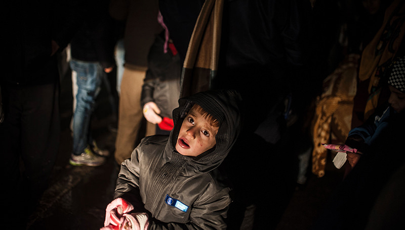A child looks on while waiting with a group of migrants to board a bus in Presevo, southern Serbia, on January 5, 2016 (AFP Photo)