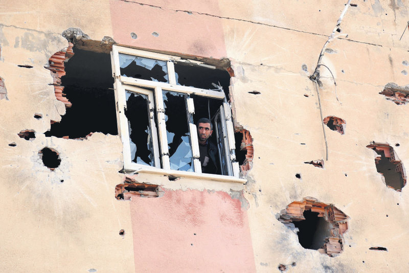 A local resident looks from a window of a house that was used by PKK terrorists in the Sur district of Diyarbaku0131r.  (Reuters Photo)