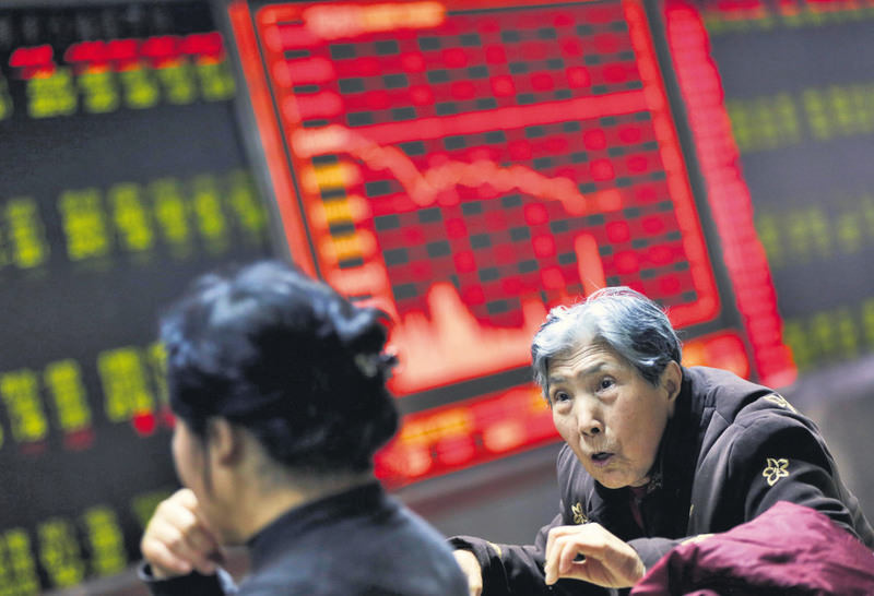 Chinese investors look at a screen showing stock movements at a stock brokerage house in Beijing, China, Jan. 4. (EPA Photo)