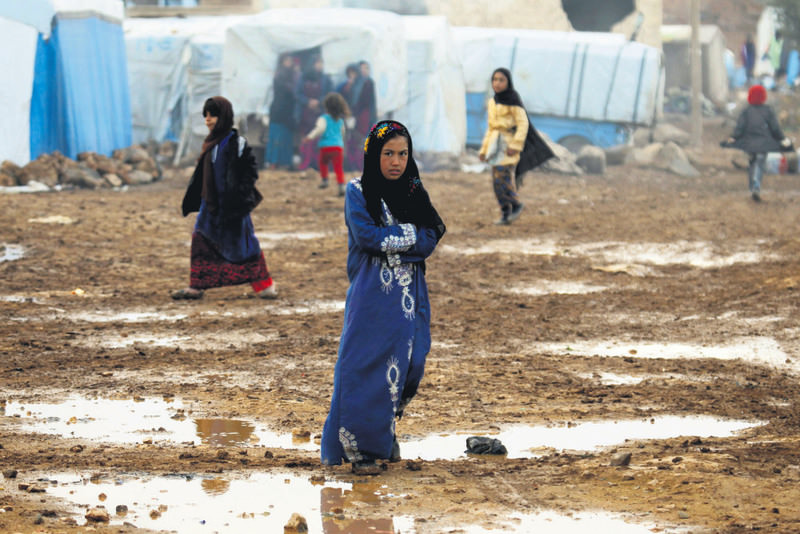 Displaced Syrian girl walking puddles of water amid a refugee camp in the Hama countryside, Syria.(Reuters Photo)