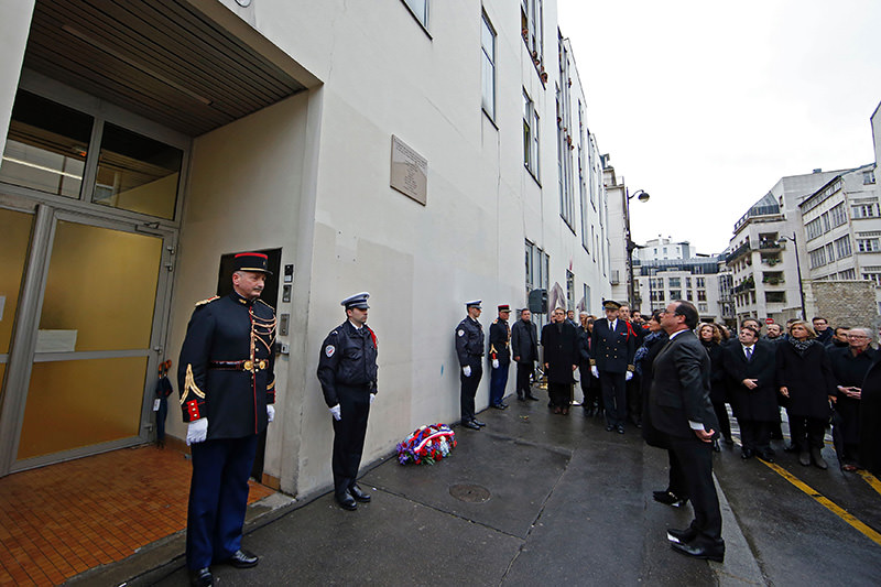 Hollande looks at commemorative plaque after its unveiling outside former offices of French weekly satirical newspaper Charlie Hebdo on Jan 5, 2016 (AFP)