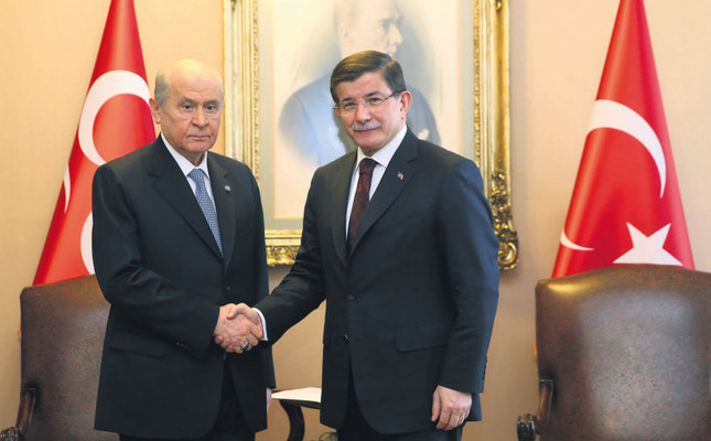 MHP Chairman Bahçeli (L) shakes hands with PM Davutoğlu following their meeting in parliament to discuss drafting a new constitution on Jan. 4. (IHA Photo)
