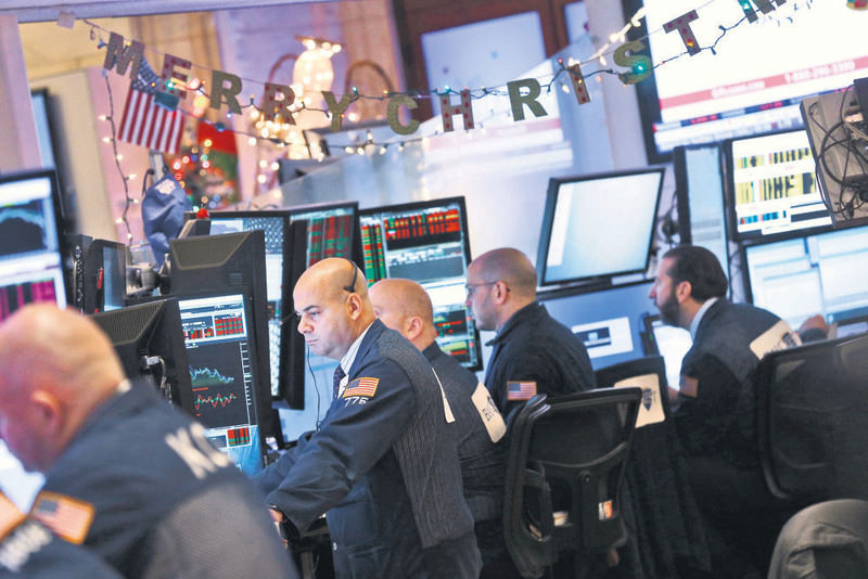 Traders work on the floor of the New York Stock Exchange (NYSE), with the sign ,Merry Christmas, in the background, at the start of the trading day in New York, on Jan.4.