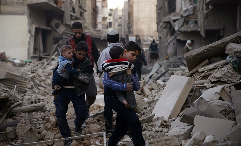 Youths carry children through a site damaged from what activists said was shelling by the Assad Regime in the town of Douma, eastern Ghouta in Damascus (Reuters Photo