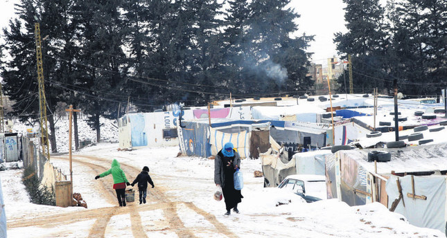 Syrian refugees walking in the snow outside their tents at the Barelias refugee camp in Beqaa Valley, eastern Lebanon.