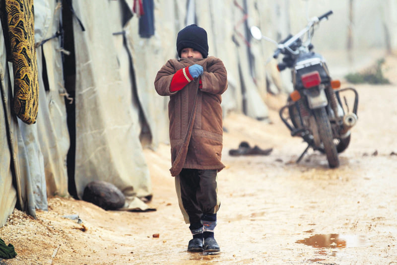 A Syrian boy walking outside tents in cold weather in Jerjnaz camp in Idlib province, Syria (Reuters Photo)