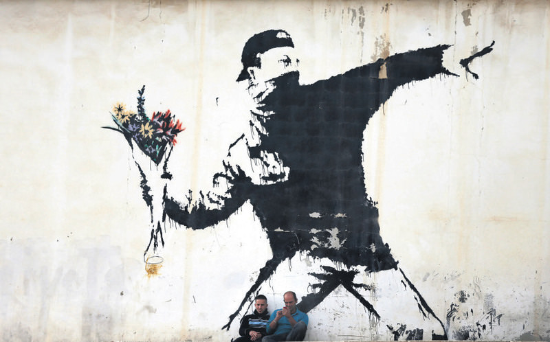 Famous graffiti of British street artist Banksy, painted on a wall of a gas station in the West Bank city of Bethlehem. (AFP Photo)