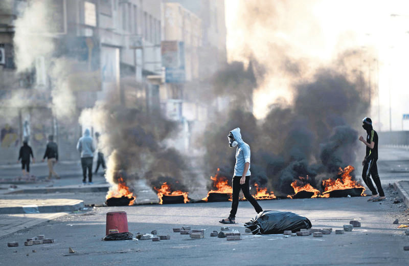 Bahraini protesters walking amid burning tyres during the clashes with riot police, following a protest against the execution of prominent Shiite cleric Nimr al-Nimr by Saudi authorities.