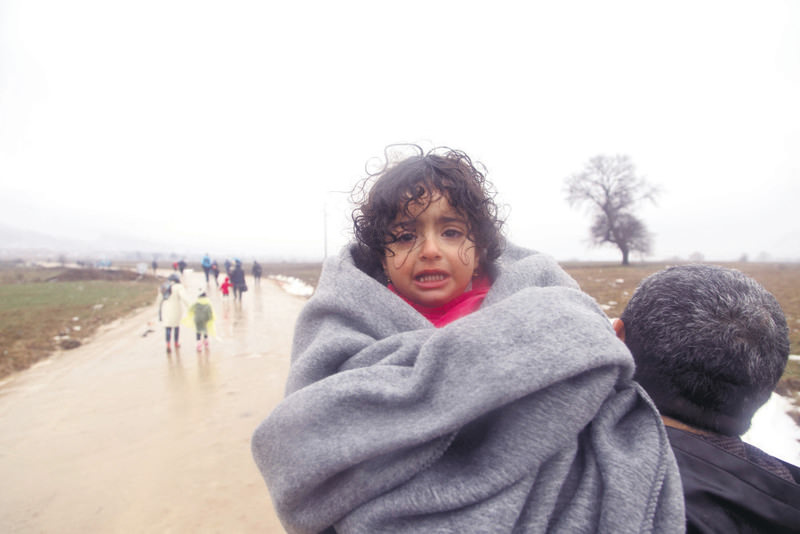 A refugee child cries as she is carried by her father from the Macedonian border to Serbia on Jan. 6.