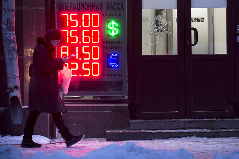 A woman walks past at an exchange office sign showing the currency exchange rates of the Russian ruble, U.S. dollar, and euro in Moscow, Russia, Monday, Jan. 11, 2016. (AP Photo)