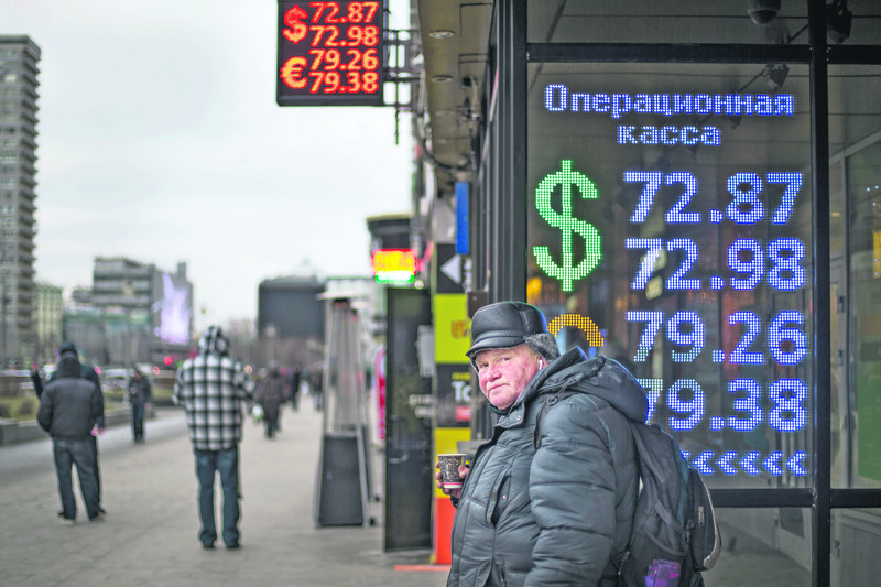 A man warms himself with a cup of hot coffee by an exchange office sign showing the currency exchange rates of the ruble, dollar, and euro in Moscow, Russia, Dec. 30.
