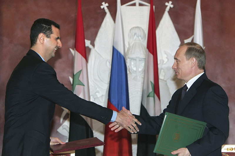 In this Jan. 25, 2005 file photo, Syriau2019s Assad, left, and Russian President Vladimir Putin shake hands during a signing ceremony in the Kremlin (AP Photo)