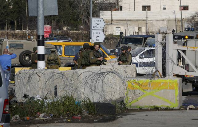 Israeli soldiers stand guard near the scene where Israeli military said a Palestinian was shot dead by Israeli troops, in the W. Bank Jan 12, 2016. (REUTERS Photo)