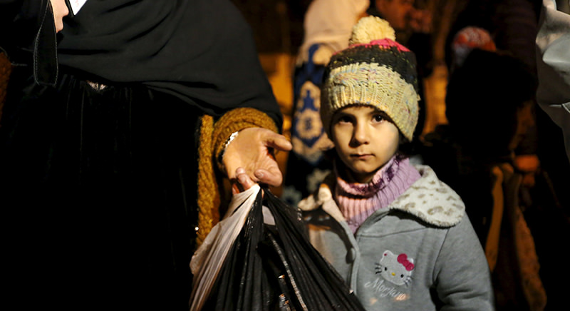 A Syrian girl waits to depart Madaya with her family, whose members say they have received permission from the Syrian government to leave the besieged town, after an aid convoy entered Madaya (Reuters Photo)