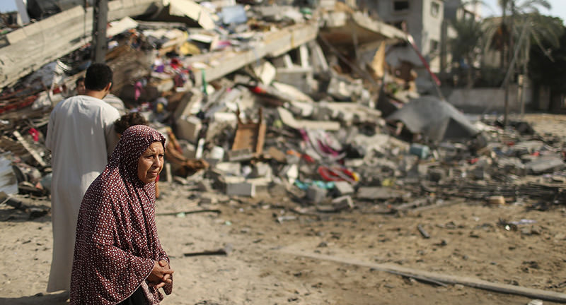 A Palestinian woman stands next to the remains of a house, which witnesses said was destroyed in an Israeli air strike, in Gaza City August 23, 2014 (Reuters Photo)