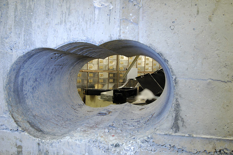 Holes were bored through a half-meter thick concrete wall drilled to access a vault in a safe deposit centre in Hatton Garden, London. (AFP Photo)