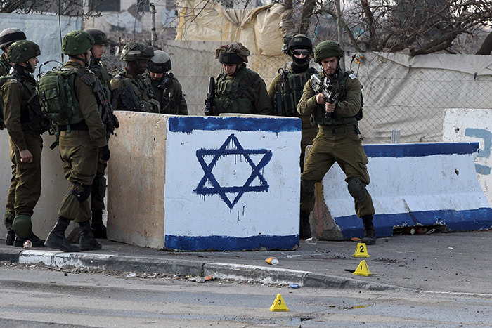 Israeli soldiers stand guard at the site of a stabbing attack at the Beit Hanoun junction near Hebron on January 12, 2016 (AFP Photo)