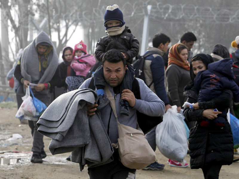 Migrants who crossed the border from Greece walk towards a transit center for refugees near the southern Macedonia's town of Gevgelija.