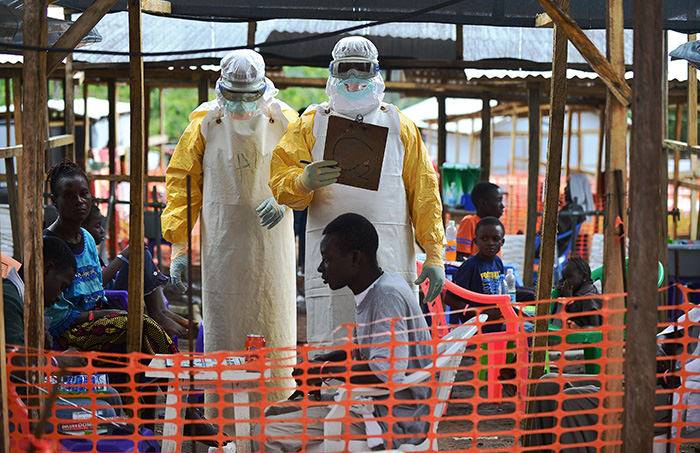 MSF medical worker, wearing protective clothing relays patient details and updates behind a barrier to a colleague at an MSF facility in Kailahun (AFP Photo)
