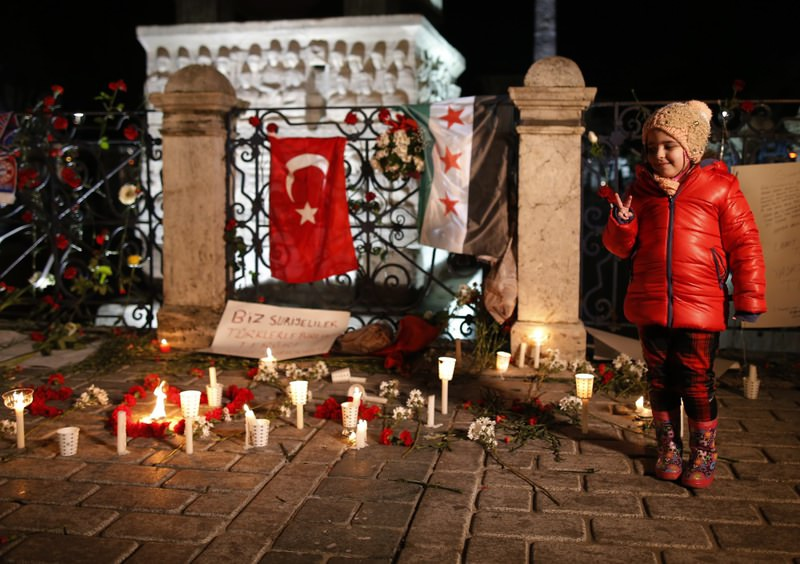 A child standing beside candles during a vigil at the site of Tuesday's explosion, Istanbul's historic Sultanahmet district.