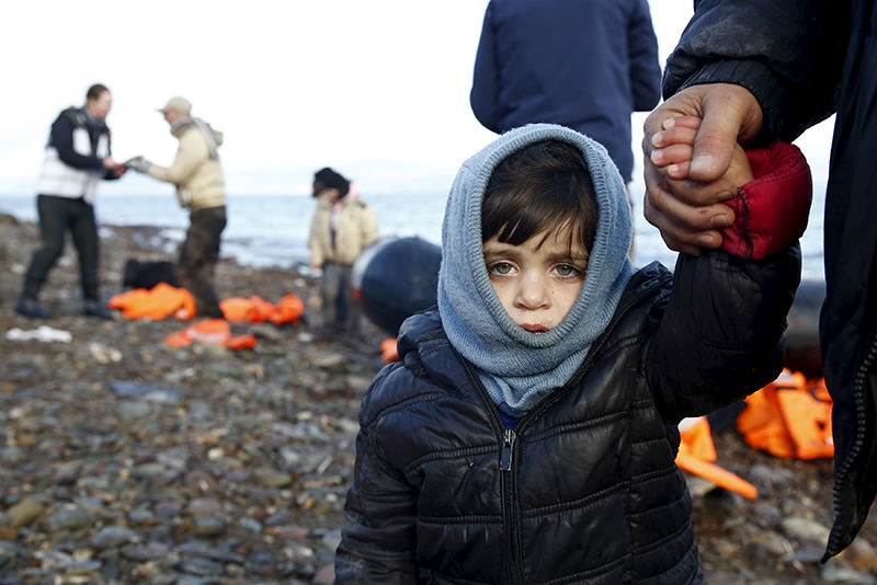 Syrian refugee child looks on, moments after arriving on raft with other Syrian refugees on a beach on the Greek island of Lesbos, Jan 4, 2016 (Reuters)