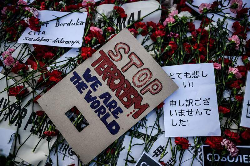A placard reading: ,Stop terrorism we are the world,, and flowers lying in tribute to victims at the site of the Jan. 12 suicide bombing in Istanbul's tourist hub of Sultanahmet Square.