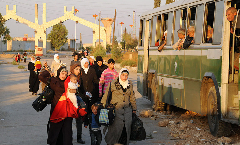 A handout picture released by the official Syrian Arab News Agency (SANA) on October 12, 2013 shows Syrian women and children arriving to be evacuated by Syria's Red Crescent from a Damascus suburb (AFP Photo)