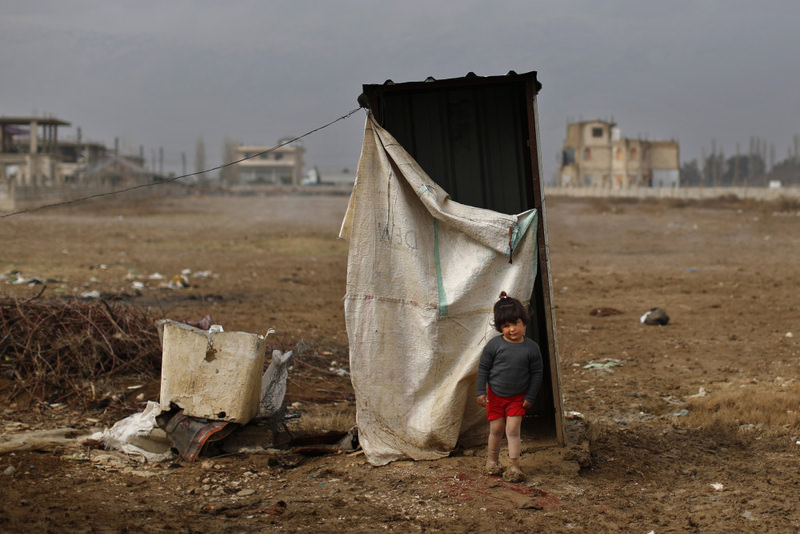 A Syrian refugee girl standing in mud from the heavy rain as she leaves a restroom at a refugee camp in the town of Hosh Hareem, Bekaa Valley in east Lebanon.