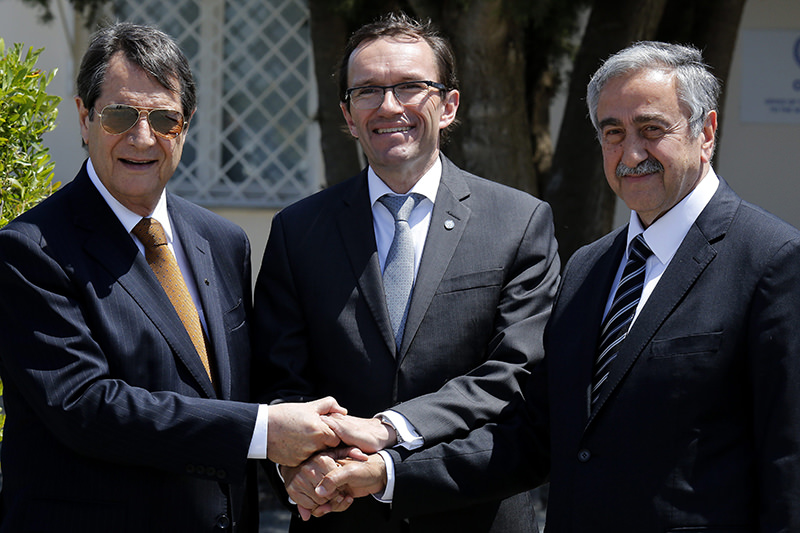 Greek Cypriot leader Nicos Anastasiades(L), Turkish Cypriot leader Mustafa Aku0131ncu0131(R), and UN envoy Espen Barth shake hands May 15, 2015. (AP Photo)