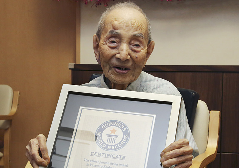 In this Aug. 21, 2015, file photo, Yasutaro Koide, 112, holds the Guinness World Records certificate as he is formally recognized as the world's oldest man at a nursing home in Nagoya (AP Photo)