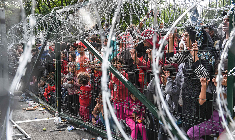 Refugees stand behind a fence at the Hungarian border with Serbia near the town of Horgos on September 16, 2015 (AFP Photo)
