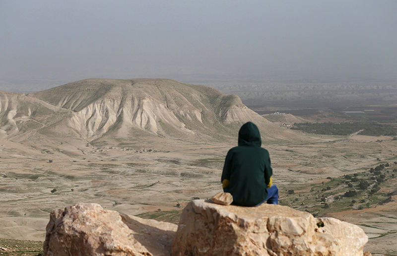 A Palestinian man sits on a rock at Jordan Valley near the West Bank city of Jericho January 21, 2016. (REUTERS Photo)