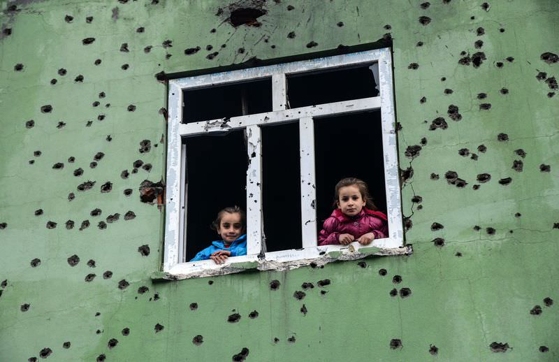 Children looking out from a window of a bullet-scarred house after the PKK militants attacked in the town of Silopi, in southeastern Turkey