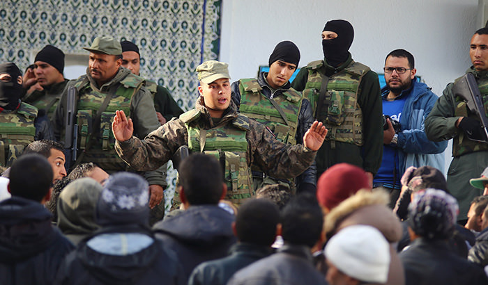 An army soldier tries to disperse protesters as he stands guard with his comrades outside the local government office during a protest in Kasserine, Tunisia January 22, 2016 (Reuters Photo)