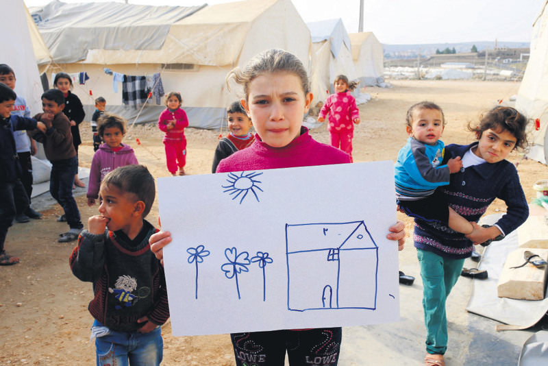Syrian refugee girl Rahaf Hasan, 10, in Turkey's Midyat refugee camp in Mardin province, poses as she holds a sketch of her home in Syria.