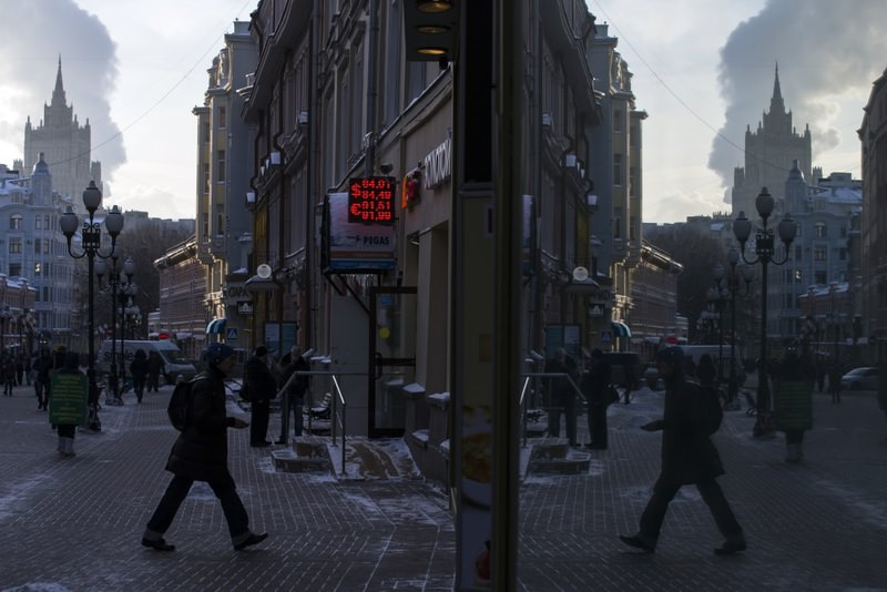 Currency exchange rates are illuminated at an exchange office as the street is reflected on a shop window in downtown Moscow. (AP Photo)
