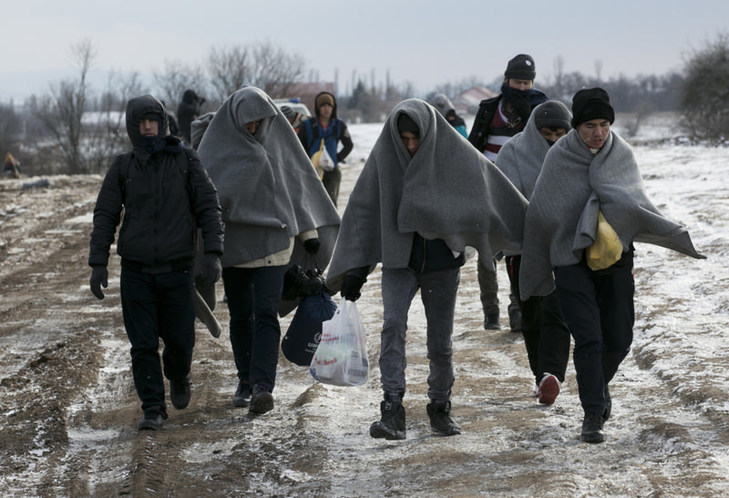 Migrants cover themselves with blankets to keep warm as they walk through snow from the Macedonian border into Serbia. (AP Photo)