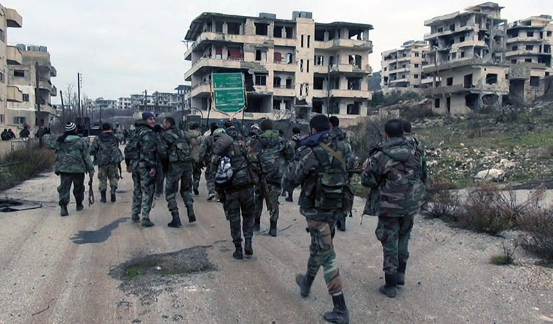 Assad forces and allied militiamen walk inside the key town of Salma in Latakia province, Syria (AFP Photo)