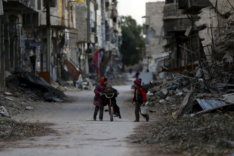 A girl pushing a boy on a bicycle past damaged buildings in Jobar, a suburb of Damascus, Syria.