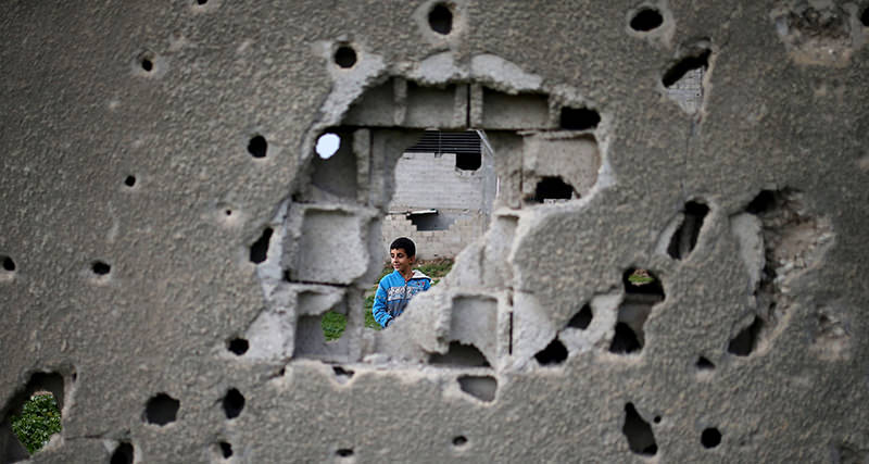A Palestinian boy is seen through a bullet riddled wall from a building which was destroyed during the 50-day war between Israel and Hamas militants in the summer of 2014, in Gaza City, on January 14, 2016 (AFP Photo)