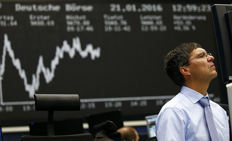 A trader works at his desk in front of the German share price index, DAX board, at the stock exchange in Frankfurt, Germany, January 21, 2016. (REUTERS Photo)