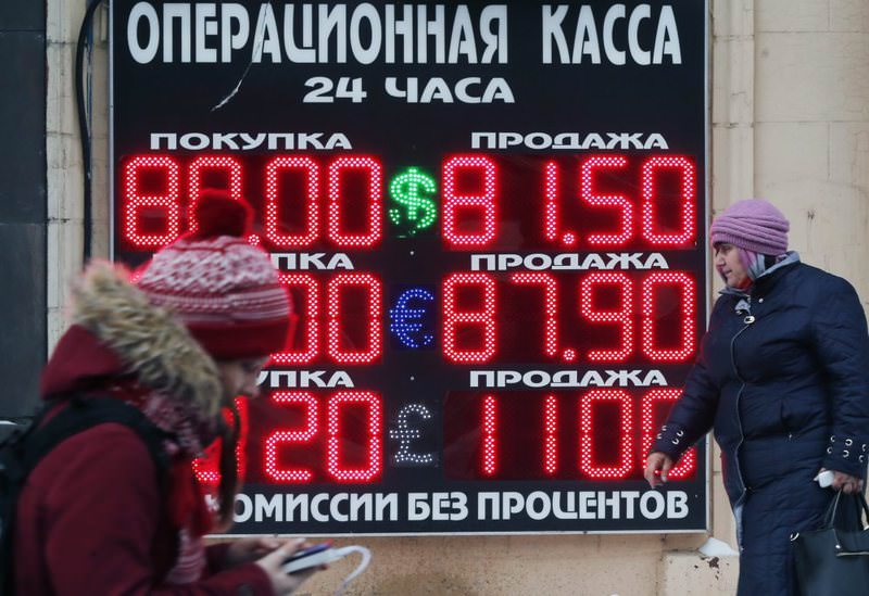 People walk past a board listing foreign currency rates against the Russian ruble in central Moscow.