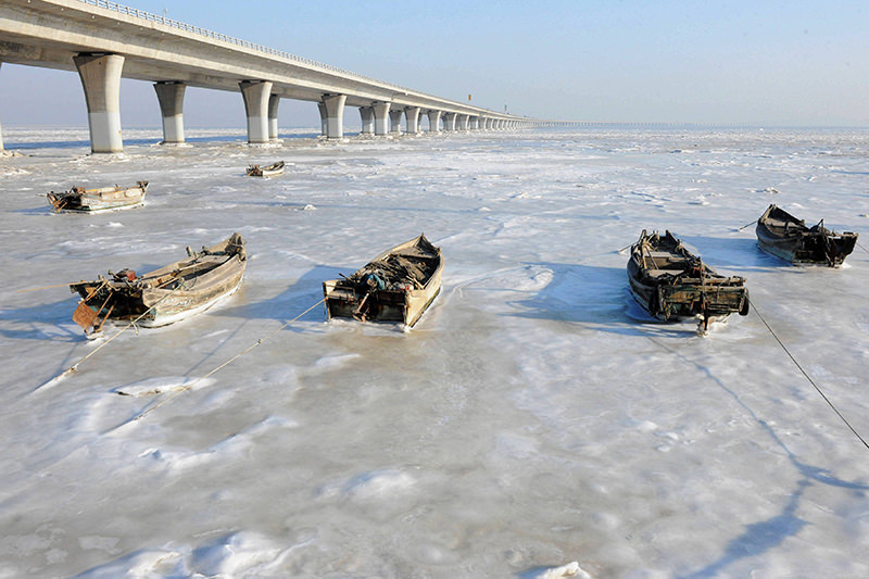 Row boats sit stuck in the ice of the frozen coastal waters of Jiaozhou Bay in Qingdao in eastern China's Shandong province on January 25, 2016. (AFP Photo)