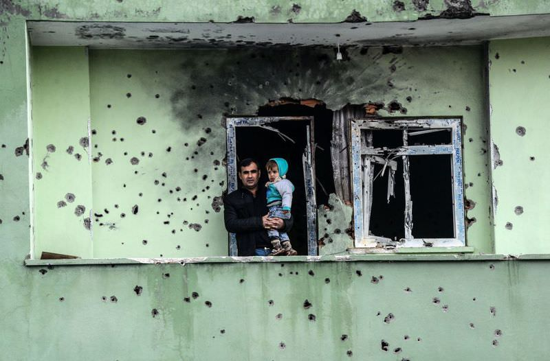 A man holding an infant stands on the balcony of a house damaged after the PKK militants' attacks in the southeastern Turkish town of Silopi.