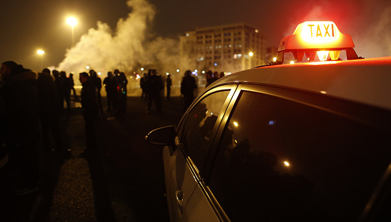 A taxi car stands in front of policemen during a demonstration on January 26, 2016 at porte Maillot in Paris (AFP Photo)
