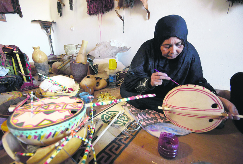 Cheynoune Zeineb, a Tuareg and imzad instrument maker, sits crossed legged while decorating an imzad with personalised Tuareg motifs in Tamanrasset in southern Algeria.