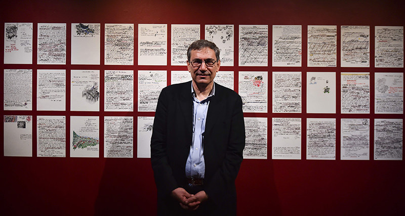 Orhan Pamuk poses with his work of art entitled 'Floating Objects' as part of his exhibition 'The Museum of Innocence' in London, on Jan 26, 2016 (AFP)