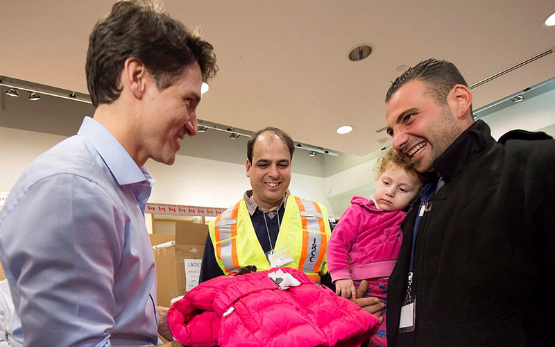 Canadian Prime Minister Justin Trudeau (Left) welcoming Syrian refugees at Lester B. Pearson Airport (Reuters Photo)