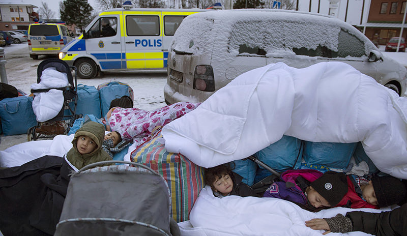 In this Jan. 8, 2016 file photo, migrant children Nor, Saleh and Hajaj Fatema from Syria sleep outside the Swedish Migration Board, in Marsta, Sweden (AP Photo)